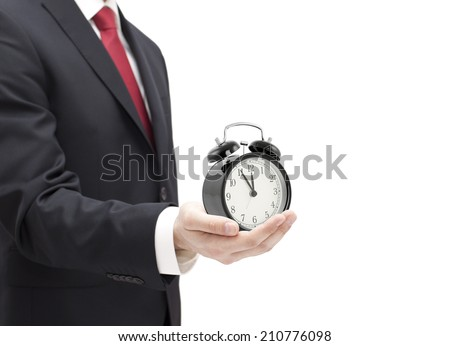 Businessman with an alarm clock in a hand isolated on white. - stock photo