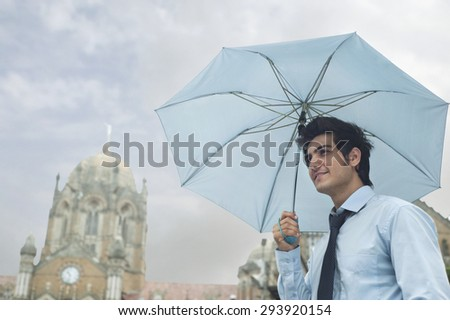 Businessman with an umbrella - stock photo