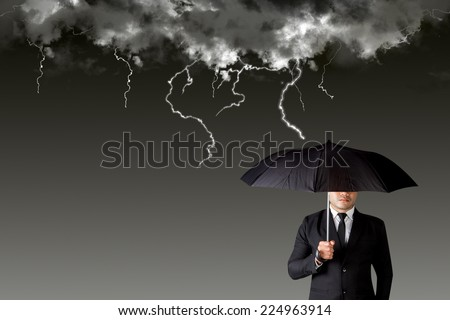 Businessman with an umbrella among rain storm and lightning concept of protection obstacle and trap on the way of a business  - stock photo
