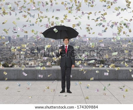 Businessman with an umbrella under the euro rain, roof terrace 2 - stock photo