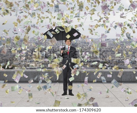 Businessman with an umbrella under the euro rain, roof terrace(all euro nominal) - stock photo