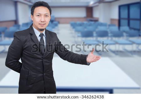 Businessman with arm out in a welcoming gesture over meeting room background - stock photo