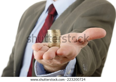 Businessman with arm outstretched showing a stack of coins - stock photo
