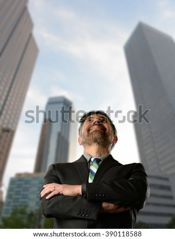 Businessman with arms crossed and looking up with tall buildings as background