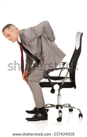 Businessman with backache standing up from a chair. - stock photo