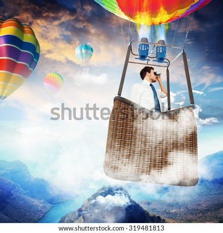 Businessman with binoculars in hot air balloon