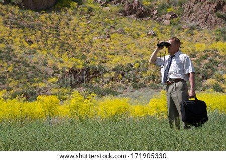 businessman with binoculars looking to the future, horizontal frame  - stock photo