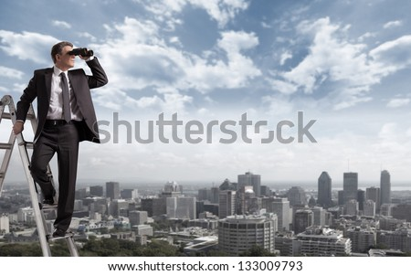 Businessman with binoculars spying on competitors.