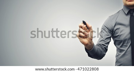 businessman with black marker on gray background with copy space
