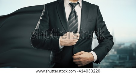 Businessman with black superhero cape on city background
