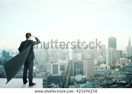 Businessman with black superhero cape standing on pedestal and looking into the distance on cityscape background - stock photo
