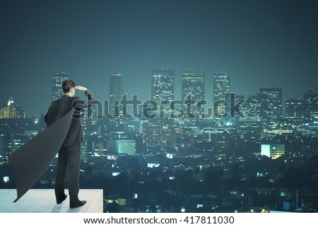 Businessman with black superhero cape standing on pedestal and looking into the distance on night city background - stock photo
