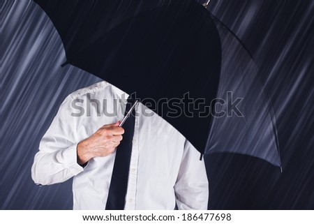 Businessman with black umbrella protecting from the rain. Business concept for protection, safety, security in hard times of economic depression. - stock photo