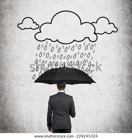 Businessman with black umbrella standing under the drawn storm.  - stock photo