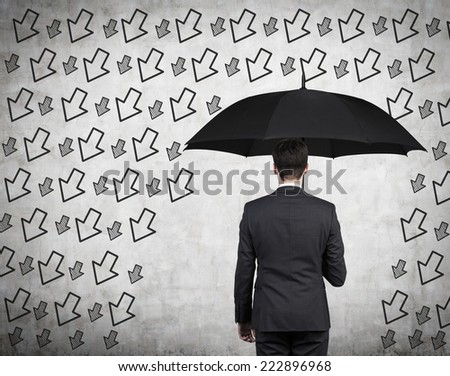 Businessman with black umbrella standing under the drawn storm of arrows. Photo over concrete background. A concept of risk avoidance.  - stock photo