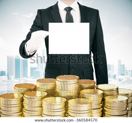 Businessman with blank white paper list in hand and stacks of gold coins, mock up  - stock photo