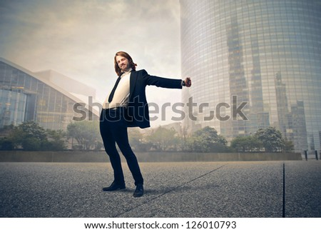 Businessman with blonde long hair stretching on a city street
