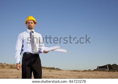 Businessman with blue prints at the field - stock photo