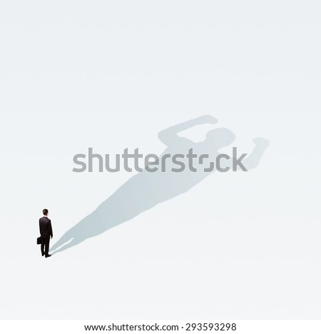businessman with bodybuilder shadow on blue floor - stock photo
