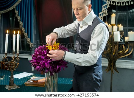 Businessman with bouquet of flowers in vase on the table