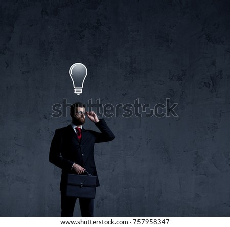 Businessman with briefcase has idea. Dark and dramatic background. Business, solution, concept.