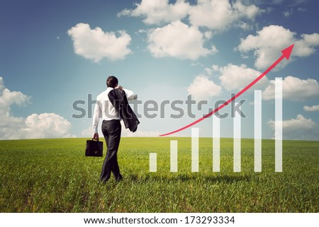 businessman with briefcase in the field with green grass and blue sky rises on the chart with red arrow up - stock photo