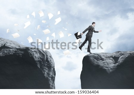 businessman with briefcase jumping  from rock to rock - stock photo