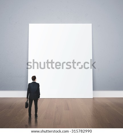 businessman with briefcase looking at blank poster - stock photo