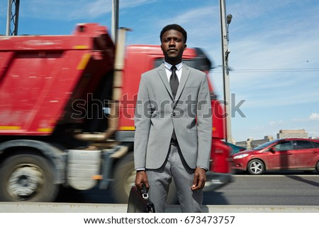 Businessman with briefcase on background of moving lorry