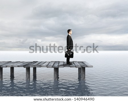businessman with briefcase standing at a pier