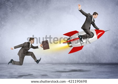 Businessman with briefcase trying to catch up flying businessman on rocket - stock photo