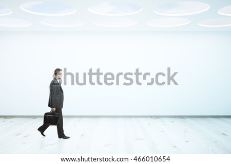Businessman with briefcase walking in abstract interior with blank concrete wall, wooden floor and round openings in ceiling, revealing blue sky. Mock up, 3D Rendering