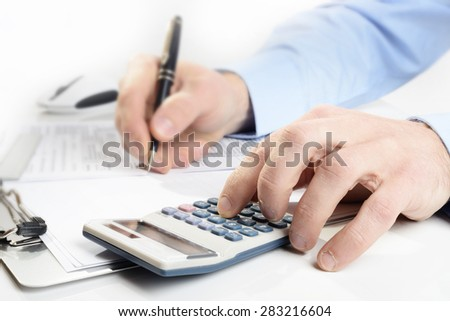 businessman with calculator  and pen focus on foreground - stock photo