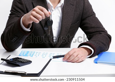 Businessman with car key in office - stock photo