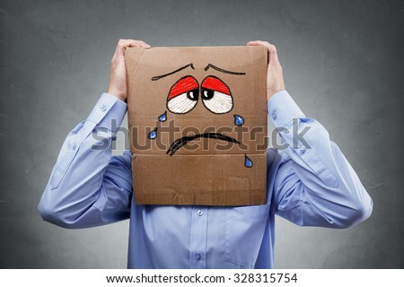 Businessman with cardboard box on his head showing a crying sad expression concept for headache, depression, sadness, heartache or frustration - stock photo