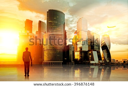 Businessman with case standing in front of Moscow city view and its reflection. Back view. Toned, filter. Concept of dream. - stock photo