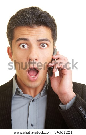 Businessman with cell phone looks shocked