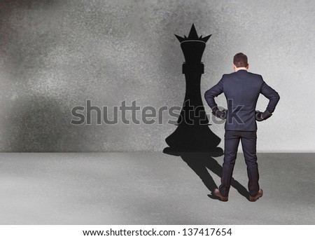 businessman with chess king shadow for street - stock photo
