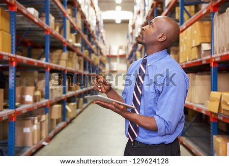 Businessman With Clipboard In Warehouse - stock photo