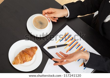 Businessman with coffee, croissant and bar chart during explanation