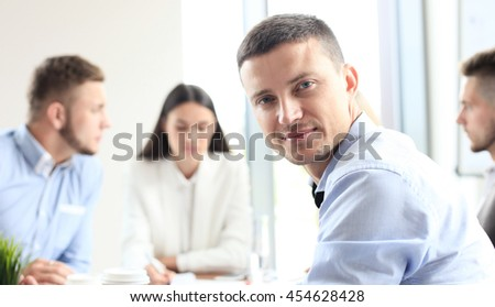Businessman with colleagues in the background in office - stock photo