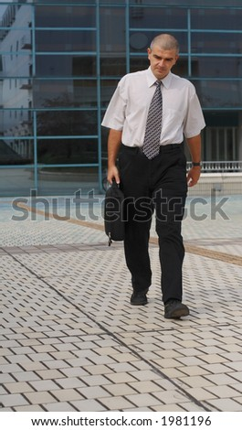 Businessman with computer bag walking in front of a corporate building
