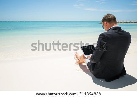 Businessman with computer on the beach - stock photo