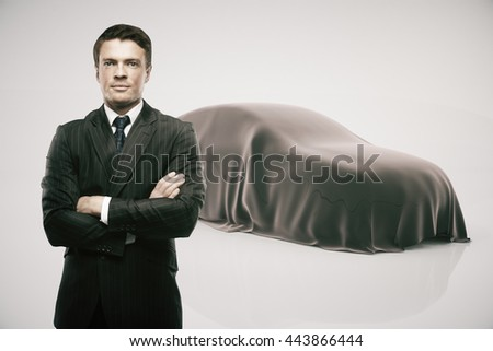 Businessman with crossed arms standing in front of car covered with grey veil on light background. Car developer presenting new product - stock photo