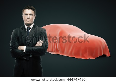 Businessman with crossed arms standing in front of car covered with red veil on dark background. Car developer presenting new product - stock photo