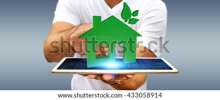 Businessman with 3D eco house and energy efficiency over tablet '3D rendering' - stock photo