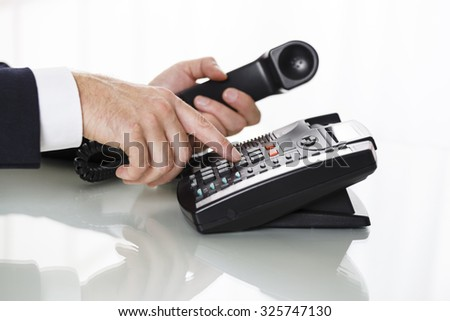 Businessman with dark gray suit dialing the number on a black landline telephone.  Closeup of his hands and the telephone on a white background. Concept of business and communication. - stock photo