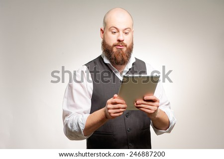 Businessman with digital tablet. Confident young caucasian bearded man in formal wear working on digital tablet while standing against gray background. - stock photo