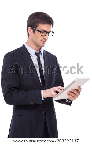Businessman with digital tablet. Handsome young man in formalwear working on digital tablet while standing isolated on white background