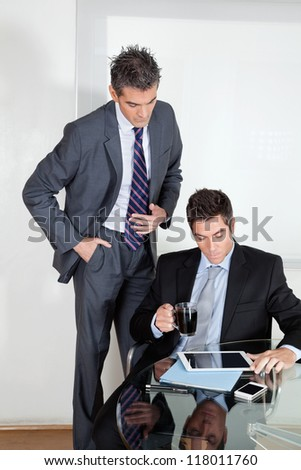 Businessman with digital tablet in a meeting with colleague at office - stock photo